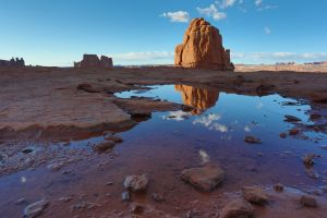 A large rock seen in a reflection at La Sal Mountains Viewpoint in Arches National Park, Utah